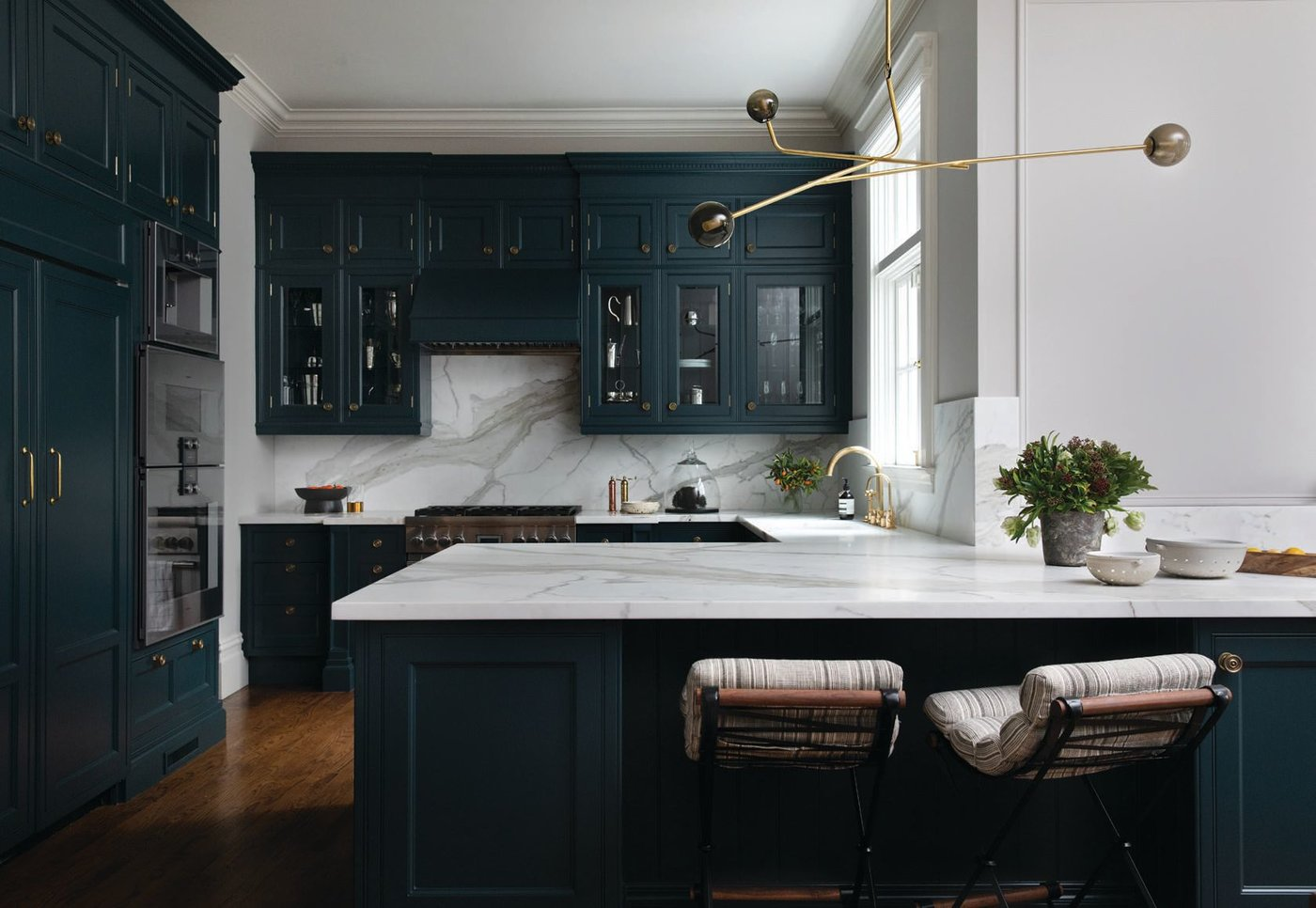 A chandelier from De La Espada presides over the kitchen, which features Thomas Hayes counter stools, Calacata Oro honed marble and a Waterworks faucet. Benjamin Moore's Narragansett Green paint coats the cabinetry PHOTOGRAPHED BY BESS FRIDAY